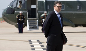 Texas Gov. Rick Perry waits to meet President Obama on the tarmac in Dallas prior to a meeting, on July 9, 2014.