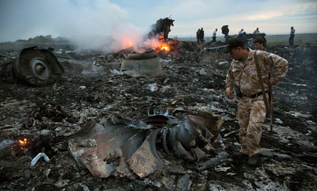 People walk among the debris of the plane after the crash Thursday.