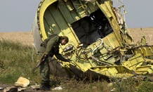 A pro-Russian rebel touches the MH17 wreckage Tuesday.