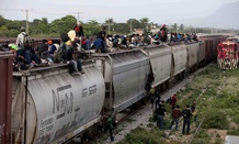 Central American migrants ride a freight train during their journey toward the U.S.-Mexico border in Ixtepec, Mexico.