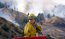Firefighter Kathleen Calvin sits atop her fire truck as smoke from a wildfire fills the sky in Winthrop, Washington.