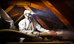 A man blows cellulose insulation in the attic of a Colorado home as part of the Energy Department's Weatherization Assistance Program.