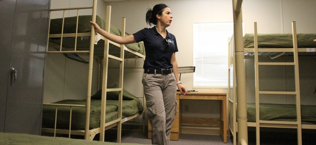 Barbara Gonzalez, public information officer for Immigration and Customs Enforcement, shows a dormitory where immigrant families are housed at the Artesia Residential Detention Facility inside the Federal Law Enforcement Center in Artesia, N.M.