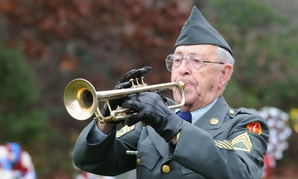 A World War II veteran plays taps at the Massachusetts National Cemetery in Bourne.