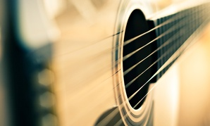 Goods that help one grow and have meaningful experiences, such as learning to play guitar,  bring happiness.