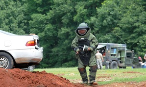 A member of the 202nd Explosive Ordnance Disposal Company runs a detonation cored from the trunk of a vehicle during a training exercise with federal and state law enforcement agencies.