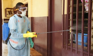Volunteers with Red Cross Society of Guinea disinfect homes and health facilities affected by the virus.