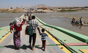 Displaced Iraqis from the Yazidi community cross the Iraq-Syria border at Feeshkhabour bridge over Tigris River Sunday.