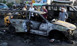 Iraqi civilians gather the morning after a string of car bombs tore through Baghdad last week.