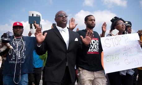 Protestors march along Florissant Road in downtown Ferguson, Mo. Monday.