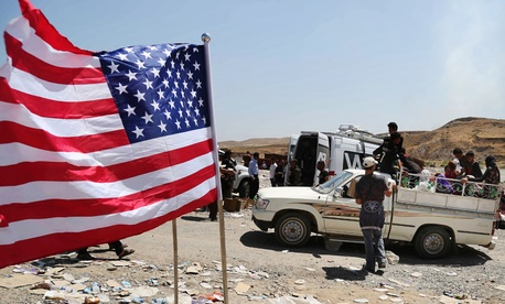 A U.S. flag waves while displaced Iraqis from the Yazidi community cross the Syria-Iraq border on Feeshkhabour bridge Sunday.