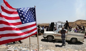 A U.S. flag waves while displaced Iraqis from the Yazidi community cross the Syria-Iraq border on Feeshkhabour bridge Sunday.