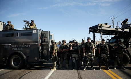 Police in Ferguson clad in SWAT gear watch protestors Wednesday.