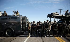 Police in Ferguson clad in SWAT gear watch protestors Wednesday.