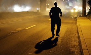 A man walks in the street after police fired tear gas to disperse a crowd Sunday.