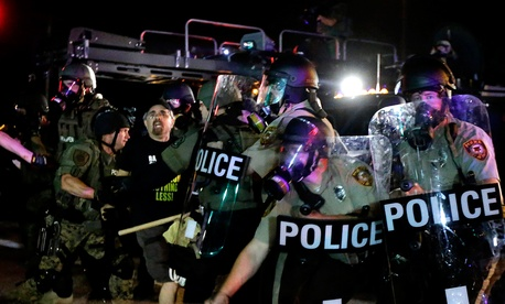 A man is detained after a standoff between protesters and police Monday in Ferguson.