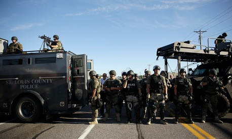 Police in Ferguson clad in SWAT gear watch protestors Aug. 9.