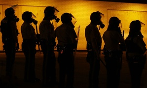 Police prepare to advance after using tear gas to disperse protesters in Ferguson, Mo.