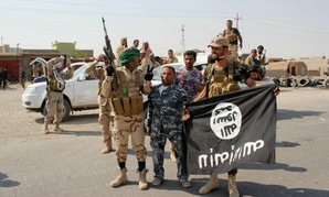 Shiite militiamen north of Baghdad, Iraq, hold the flag of the Islamic State group they captured.