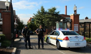 Guards watch the entrance of the Washington Navy Yard, where last year's shooting by contractor Aaron Alexis has prompted questions about the security clearance process.