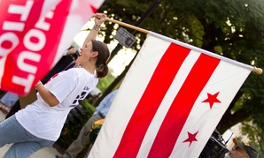 An attendee supporting statehood carries a DC flag during an event in 2012.
