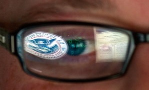 A reflection of the Department of Homeland Security logo is seen reflected in the glasses of a cyber security analyst at DHS.