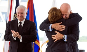 Defense Secretary Robert Gates, left, applaud as Letitia Long, center, is hugged by James Clapper, director, National Intelligence, center, after becoming the new Director of the National Geospatial-Inteligence Agency, Monday, Aug. 9, 2010.