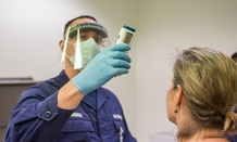 A Coast Guard employee working with CBP's Office of Field Operations checks the temperature of a traveler at Dulles airport who has recently been to Guinea, Sierra Leone or Liberia.