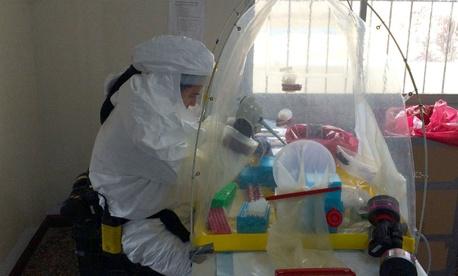 U.S. Navy Lt. Jose Garcia prepares samples for further analysis at a Naval Medical Research Center mobile laboratory at Bushrod Island, Liberia.