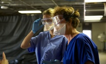 Health care workers learn the proper protocols for personal protective equipment during a CDC Ebola training course.