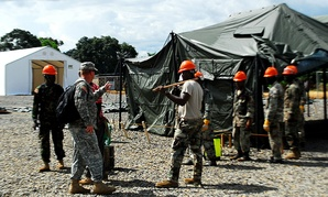 Troops help build an Ebola treatment center in Liberia.  Military members must go into quarantine when they leave West Africa.