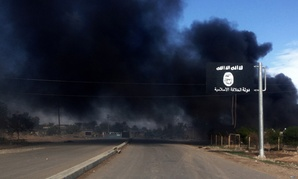 Smoke billows behind an Islamic State group sign during clashes between militants from the Islamic State group and Iraqi security forces in Iraq.