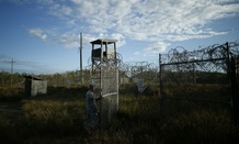 A soldier closes the gate at the now abandoned Camp X-Ray at Guantanamo in 2013.