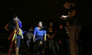 A group of immigrants from Honduras and El Salvador who crossed the U.S.-Mexico border illegally are stopped in June 2014, in Granjeno, Texas.