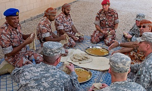 U.S. linguists share a meal with Omanis and British Foreign Service Officers in 2012.