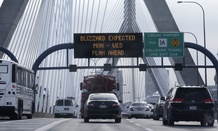 With a road sign warning of an expected blizzard, morning commuters travel across the Zakim Bunker Hill Bridge into downtown Boston., Monday, Jan. 26, 2015.