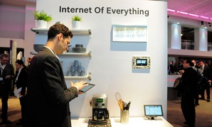 """A man checks his device in front of a banner """"Internet of Everything"""" at the Mobile World Congress."""