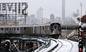 A New York City subway train runs along a section of elevated track in Queens following the system's reopening on Tuesday.