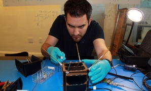 A Spire employee works on one of the company's satellites.