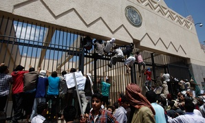 Yemeni protestors climb the gate of the U.S. Embassy in 2012.