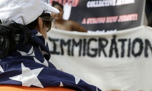 U.S. flag drapes over the shoulders of Maria Almanza as immigration reform supporters gather outside of the hall of records in Freehold, N.J., in 2013.
