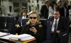 Then Secretary of State Hillary Clinton working aboard a C-17 aircraft bound for Libya in 2011.