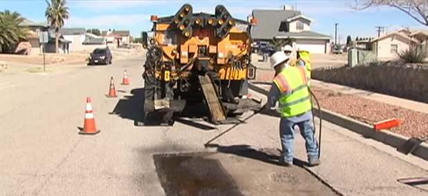 An El Paso work crew repairs a pothole on a residential street.