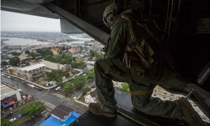 U.S. Marine Corps Cpl. Anthony Kite looks out of an MV-22B Osprey as it prepares to land at the U.S. Embassy in Monrovia, Liberia, to support Operation United Assistance.