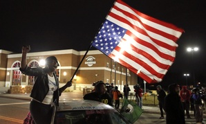 Gina Gowdy joins protesters on the street outside a Ferguson, Missouri, fire station, Wednesday, March 4, 2015, in Ferguson.