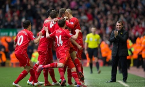 Liverpool manager Brendan Rodgers claps as his team celebrates a goal.