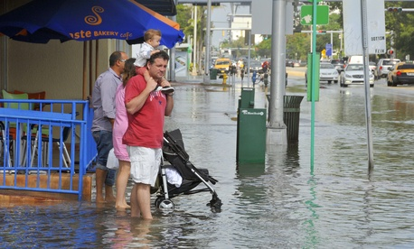 People in Miami Beach's South Beach area wade through high water in October 2012.