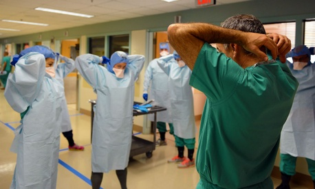 Navy Cmdr. James Lawler trains a team that would deploy in the event of a U.S. Ebola crisis on how to use personal protective equipment.