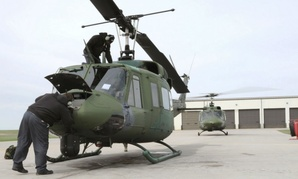 Mechanics at Minot Air Force Base, N.D., inspect a UH-1N Huey.