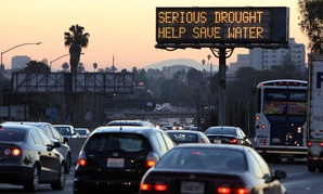 Morning traffic passes a sign in Los Angeles in July warning of drought.